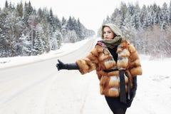 Bella ragazza in una pelliccia che aspetta l'automobile su una strada di inverno nella foresta Fotografia Stock