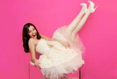 Bella ragazza in vestito bianco divertendosi sulla tavola Immagine Stock