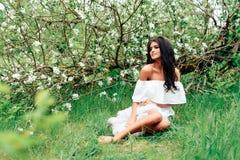 Bella ragazza in vestito bianco nei meleti sboccianti di primavera Fotografia Stock