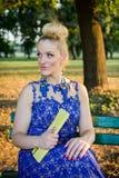 Bella ragazza in vestito che si siede sul banco Fotografie Stock