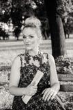 Bella ragazza in vestito che si siede sul banco Fotografia Stock