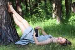 Bella ragazza in vestito che si trova sull'erba sotto l'albero con il libro Immagini Stock