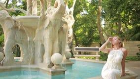 Bella ragazza in vestito che sta fontana di pietra d'annata vicina stock footage