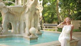 Bella ragazza in vestito che sta fontana di pietra d'annata vicina archivi video