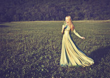 Bella ragazza in vestito da verde lungo con il mazzo dei fiori in onnature di estate fotografia stock libera da diritti