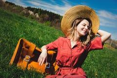 Bella ragazza in vestito e cappello rossi con la valigia che si siede sul prato fotografia stock
