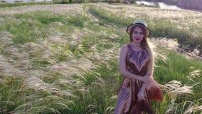 Bella ragazza in vestito e cappello sul campo nel tramonto archivi video