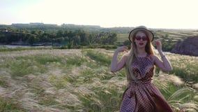 Bella ragazza in vestito e cappello sul campo nel tramonto video d archivio