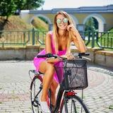 Bella ragazza in vestito rosa su una bicicletta fotografie stock