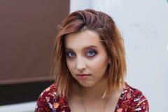 Bella ragazza in vestito rosso che posa per la macchina fotografica fotografia stock