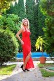 Bella ragazza in vestito rosso che posa su un fondo degli alberi Fotografie Stock Libere da Diritti