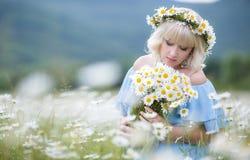 Bella ragazza in vestito sul giacimento di fiori della margherita Fotografia Stock