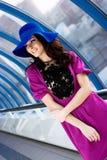 Bella ragazza in vestito viola e cappello blu Immagini Stock Libere da Diritti