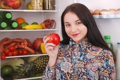 Bella ragazza vicino al frigorifero con alimento sano immagini stock