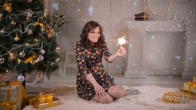Bella ragazza vicino alla stella filante della tenuta dell'albero di Natale, fuoco del Bengala Celebrazione del natale archivi video