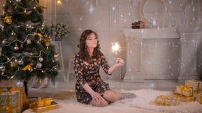 Bella ragazza vicino alla stella filante della tenuta dell'albero di Natale, fuoco del Bengala Celebrazione del natale video d archivio