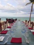 Bella regolazione della tavola in bianco ed in rosso accanto alla spiaggia in Bahamas Vetro di vino di cristallo blu e tovaglioli fotografia stock