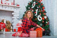 Bella rete della donna all'albero di Natale, vestito rosso Immagine Stock Libera da Diritti
