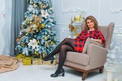 Bella rete della donna all'albero di Natale, vestito rosso Fotografia Stock