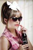 Bella retro ragazza che tiene una vecchia coca d'annata Immagine Stock