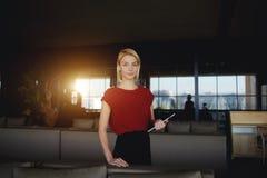 Bella riuscita donna di affari che posa con la compressa digitale mentre aspettare partner in ristorante di lusso Fotografia Stock