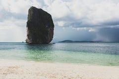Bella roccia sulla spiaggia con le nuvole scure, Krabi, Tailandia Immagine Stock