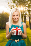 Bella scatola bionda della tenuta della ragazza con un regalo fotografia stock