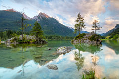 Bella scena degli alberi su un'isola della roccia e delle montagne al sunri Fotografie Stock