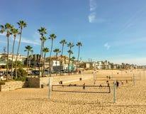 Bella scena della spiaggia di California del sud con pallavolo, le palme, il sole e le case della riva immagine stock libera da diritti