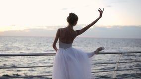 Bella scena di una ballerina di dancing in tutu bianco e di un pointe sull'argine sopra la spiaggia del mare o dell'oceano al tra stock footage
