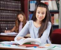 Bella scolara adolescente con i libri che si siedono dentro Fotografie Stock
