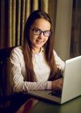 Bella scolara in camicia ed occhiali bianchi facendo uso del computer portatile fotografie stock libere da diritti