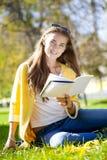 Bella scolara che si siede nel parco di autunno e che legge un libro Immagine Stock