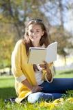 Bella scolara che si siede nel parco di autunno e che legge un libro Fotografie Stock