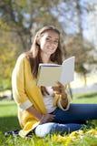 Bella scolara che si siede nel parco di autunno e che legge un libro Immagine Stock Libera da Diritti