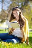 Bella scolara che si siede nel parco di autunno e che legge un libro Fotografia Stock Libera da Diritti