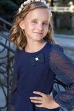 Bella scolara dolce della ragazza in uniforme scolastico fuori un giorno soleggiato con capelli ricci e una corona delle rose del Fotografia Stock