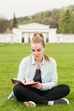 Bella scrittura della donna in suo diario che si siede nel parco Fotografia Stock
