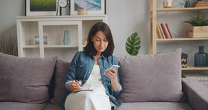 Bella scrittura della ragazza in taccuino che esamina lo schermo dello smartphone che si siede a casa stock footage