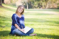 Bella scrittura femminile teenager in un libro all'aperto Immagini Stock Libere da Diritti