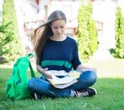 Bella scuola o studentessa di college che si siedono sull'erba con i libri e borsa che studia in un parco Immagini Stock Libere da Diritti