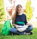 Bella scuola o studentessa di college che si siedono sull'erba con i libri e borsa che studia in un parco Fotografie Stock Libere da Diritti