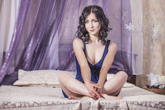 Bella seduta castana della donna sul letto con un baldacchino in Immagini Stock Libere da Diritti