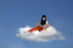 Bella seduta femminile con il computer portatile sulla nuvola Immagini Stock