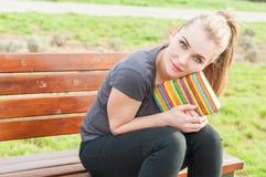 Bella seduta femminile felice sul banco fuori con il suo diario Immagine Stock