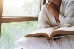 Bella seduta femminile sul letto e sulla lettura un libro Fotografie Stock