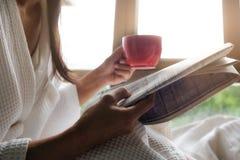 Bella seduta femminile sul letto e sulla lettura un libro Fotografia Stock