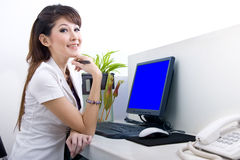 Bella segretaria con lo schermo di computer in bianco Immagine Stock