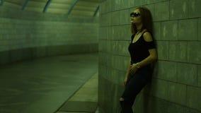 Bella signora alla moda in vestiti scuri che posano sulla macchina fotografica nel sottopassaggio video d archivio