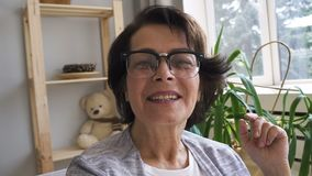 Bella signora anziana sta parlando, avendo buon tempo nell'interno domestico archivi video